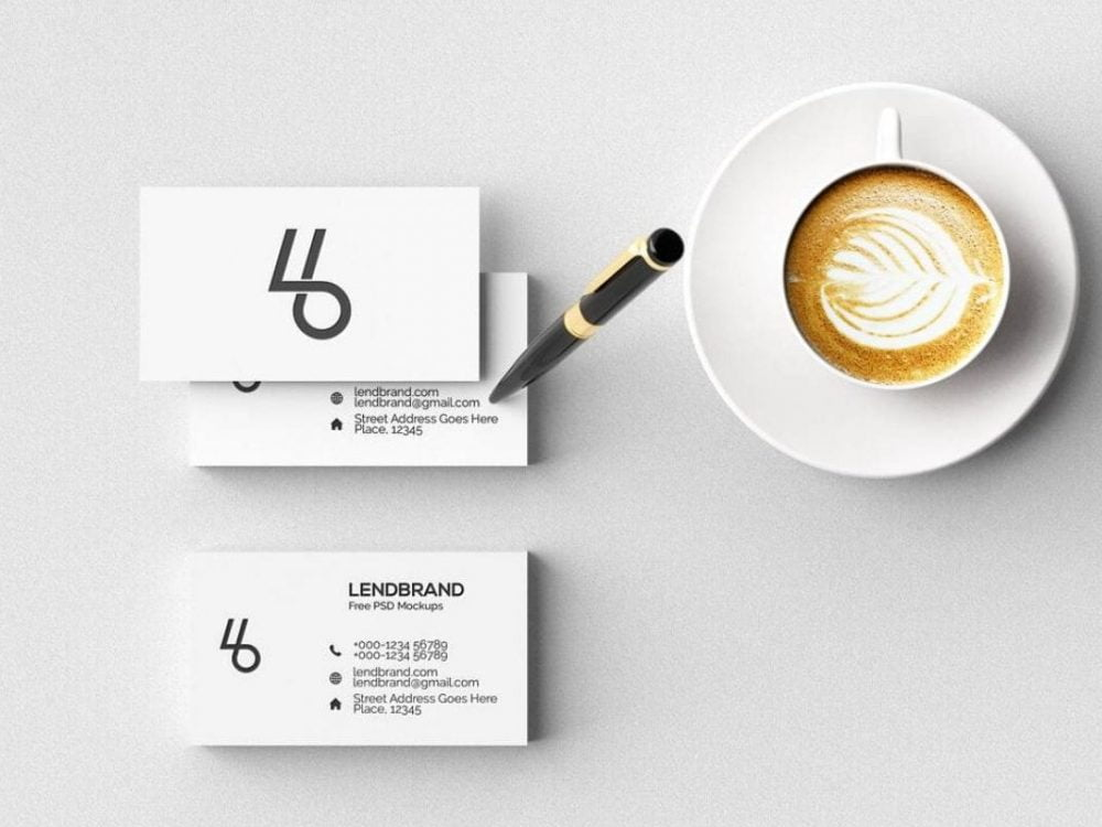 Mockup of a Business Card Being Held Next to a Coffee Cup